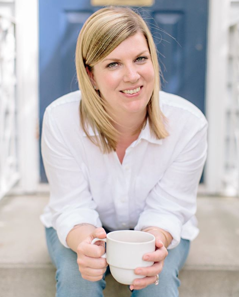 Kara from blue_alice_space_design sitting on a doorstep with a white shirt and jeans, and white coffee cup
