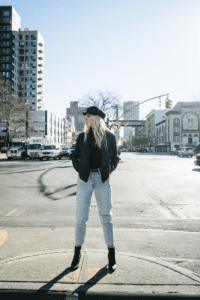 Carly Mal in Fall Fashion standing on city street with black har and jacket