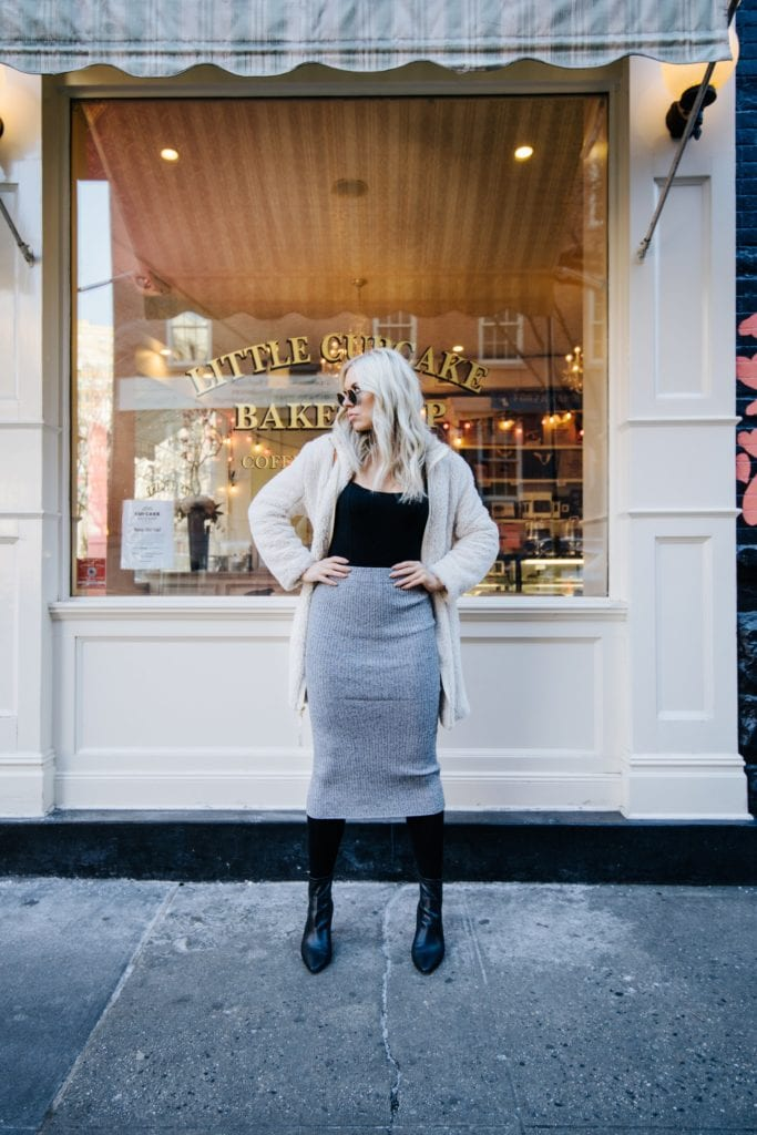 Carly Mal in a pencil skirt and sunglasses in front of a bakery