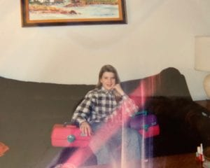 Kara from Blue Alice Space Design at 13 years old sitting on a couch with a flannel shirt