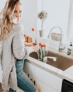 Stesha (@stesharose), family and fashion blogger and trend setter, organizing tulips in a vase in her kitchen sink, wearing a cozy sweater and jeans