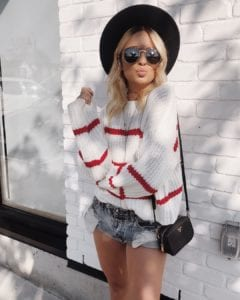 Tessa (@tessalindsaygarcia) is a fashion blogger from Vancouver that frequents the Okanagan; here she is standing against a white brick wall wearing a white sweater with red stripes, jean shorts, sunglasses, and a black hat